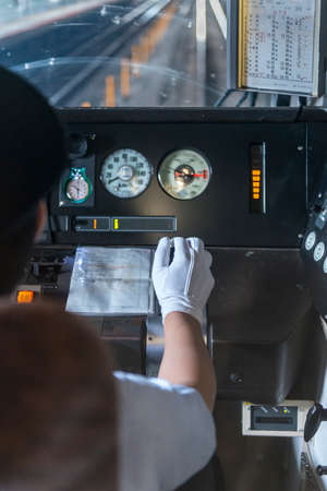 The white gloved hand of a Japanese train driver on the regulator in a train cab