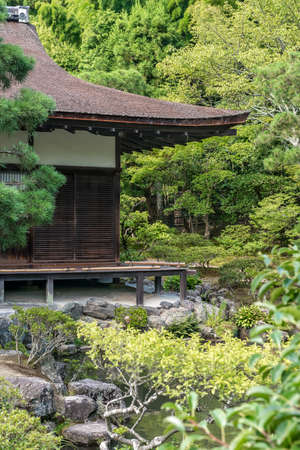 A traditional Japanese wooden building surrounded by trees in a formal garden setting
