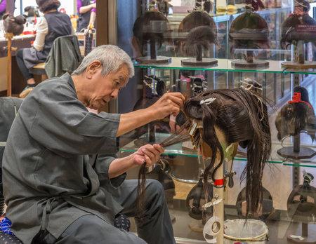 장인은 작업장에서 전통적인 사무라이 가발을 만듭니다