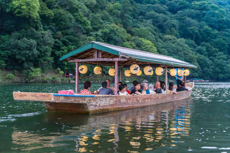 Tourists on a boat used for watching cormorant fishing on the Katsura River in Arashiyama Editorial