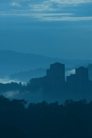neighborly: Misty morning of high rise buildings on hilly residential area.