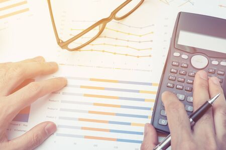 Business man Using calculator analyzing investment chart on the desk working at office. business concept.