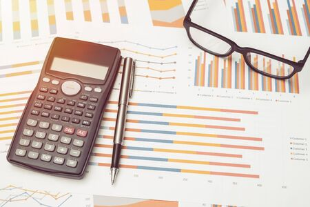 Data analysis with calculator from charts on desk at office. business concept. Stock fotó