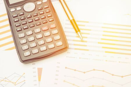 Data analysis with calculator from charts on desk at office. business concept. Stok Fotoğraf