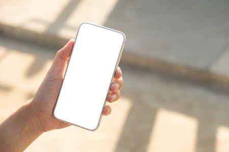 Frauenhand, die Smartphone mit leerem Bildschirm im Park hält und benutzt Standard-Bild
