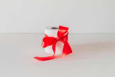 papier toilette avec un arc rouge sur fond blanc. Banque d'images