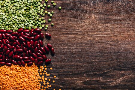 Three types of legumes, beautifully laid out on a wooden background - red beans, green peas and orange lentils. Top view. Vegetarian food. Unprepared.
