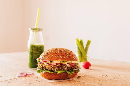 Vegetarian burger with a bottle of green smoothie and carrot with celery in a glass. Stone beige table