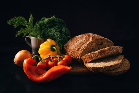 vegetables and sliced bread on a dark background