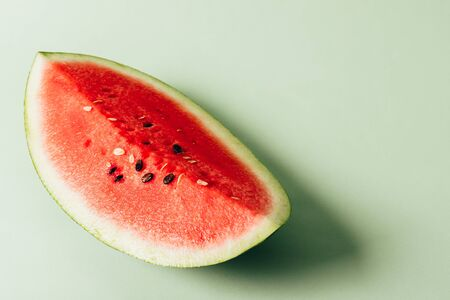 A piece of red juicy watermelon lies on a green background. fruit. Copy space