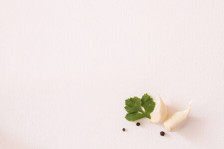 two young garlic with cilantro and black peppercorns on a white background. Copy space. Фото со стока