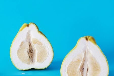 sliced pomelo bright yellow green on a blue background. isolated. copy space Stok Fotoğraf