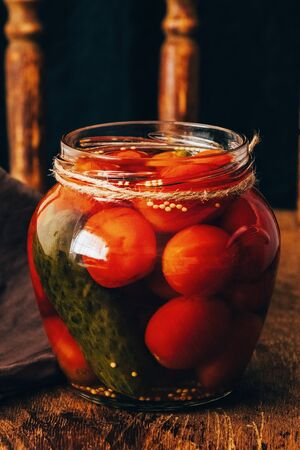 fermented tomatoes in transparent glass jars . On a wooden vintage background. cucumber