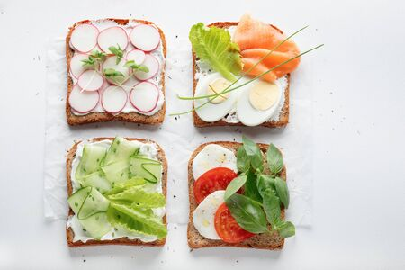 sandwiches with mascarpone cheese, cucumber, radish, eggs, caprese salad, salmon on a white background. top view. copy space.