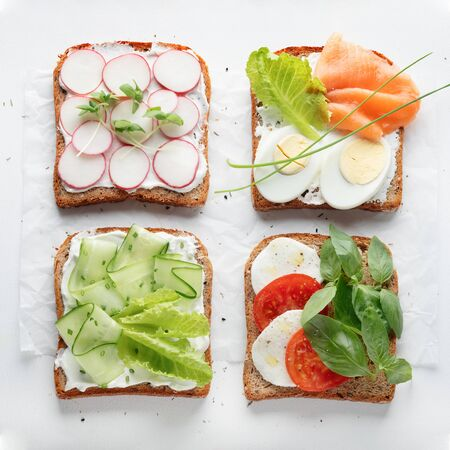 sandwiches with mascarpone cheese, cucumber, radish, egg, caprese salad on a white background. top view. close Stock Photo