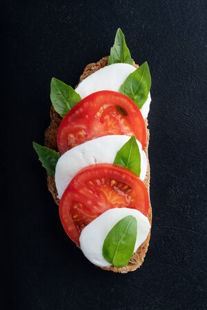 sandwich with caprese salad on a black background. close up. top view.