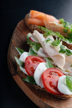ham, radish sandwiches, with mascarpone cheese, caprese salad on a wooden, black background. close up
