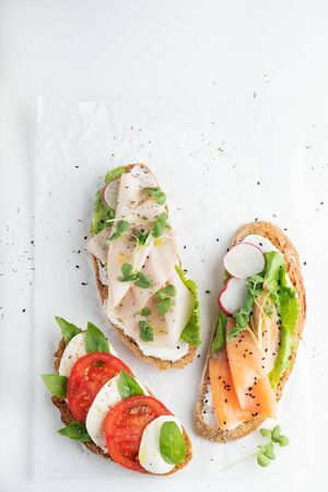 sandwiches with ham, radish, romano salad, baby basil, mascarpone cheese, caprese salad, spiced olive oil on a white background. copy space. top view.