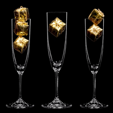 Small golden gift boxes inside champagne glasses on the black background  Stock Photo