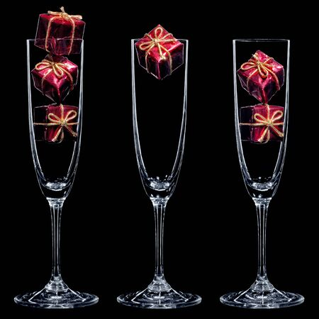 Small red gift boxes inside champagne glasses on the black background