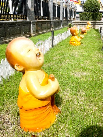 kid monk mini figure acting on grass unusual photo