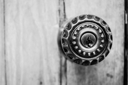 closeup the part of door lock with metal knob on wood