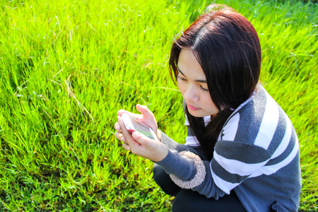young beautiful asian girl romantic teenage model enjoy with smartphone on the green grass meadow field in sun light photo