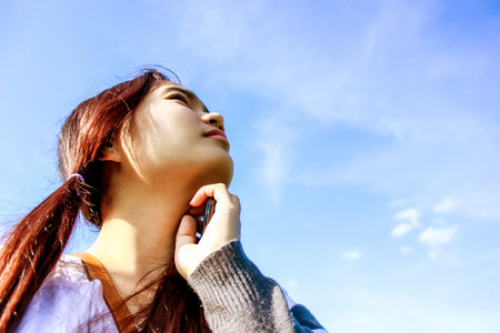 young beautiful asian girl romantic teenage model enjoy thinking with blue sky on the green grass meadow field in sun light photo