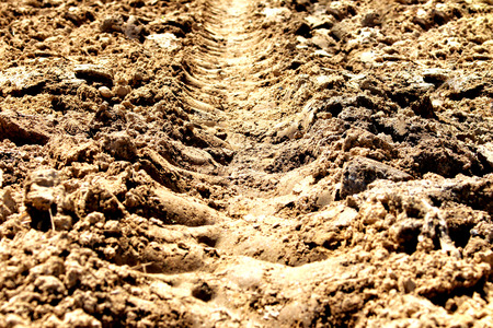 traces of the wheel off-road truck tire on the dried soil background pattern photo