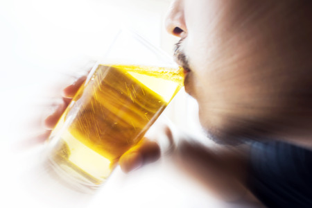 man drinking canned beer with motion blur photo