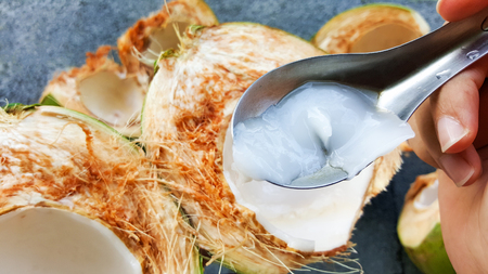 use spoon picking up young green coconuts with nutrient, health benefits, dietary fiber and high electrolytes Stock Photo