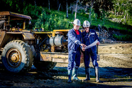 excavating machine: Mine head and mine foreman discussing plans in front of excavating machine