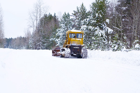 grader: Crawler Tractor grader cleans snow on a forest road. Winter background. Medium shot.