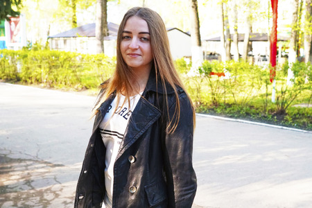 sensation: Fatigue. A young pretty girl with light brown hair depicts different emotions. The girl is dressed in a black leather jacket and a white dress under her. She does this by walking in the spring park. Sunny spring evening. Stock Photo