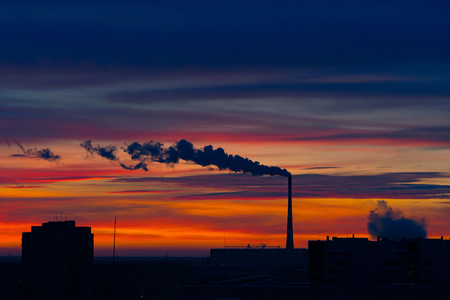 Early winter morning over the city. Red-blue bright sky. The sun has not yet risen. The city begins to wake up.  Only the pipe already in full smokes.