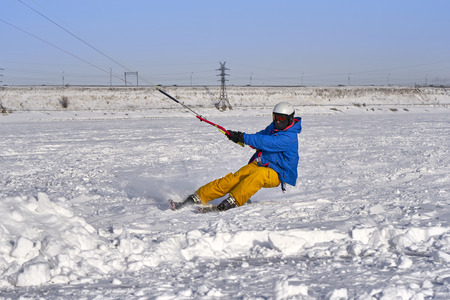A male athlete engaged in snow kiting on the ice of a large snowy lake. He goes skiing in the snow. Winter sunny frosty day.