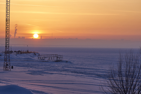 A winter sunset over a large frozen lake. On the far bank in the haze are visible silhouettes of buildings. A quiet frosty winter evening. Stock Photo