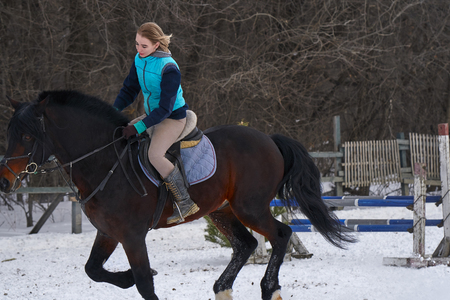 A girl on a horse  jumps  gallops. A girl trains riding a horse in a small paddock. A cloudy winter day.