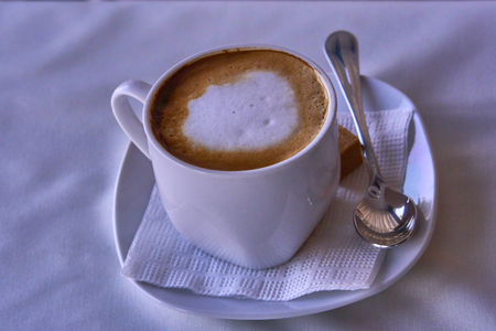 A cup of morning coffee. Porcelain white cup of cappuccino coffee on a table with a white tablecloth. Close-up.