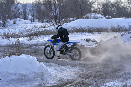 Sportsman racer man fulfills a fast ride on a motorcycle on the road extreme. The race track is very uneven.  Photo as the racer passes the turn. A sunny winter day. 스톡 콘텐츠 - 97010969