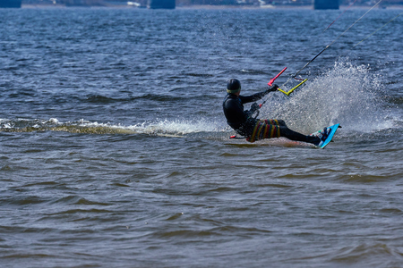 A male kiteboarder rides on a board on a large river. He performs various exercises while moving on water. Splashes of water scatter in different directions. The suns rays shine in the water. Sunny s 写真素材