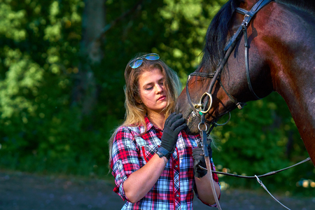 Beautiful girl with long hair on a walk with a horse. Summer evening. Stockfoto