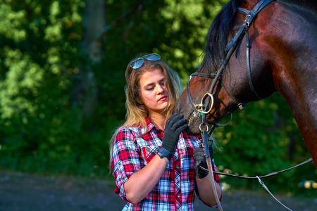 Schönes Mädchen mit langen Haaren auf einem Spaziergang mit einem Pferd. Sommerabend.