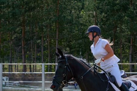 Young woman jockey in white dress and black boots, takes part in equestrian competitions. Close-up. Banco de Imagens - 108049342