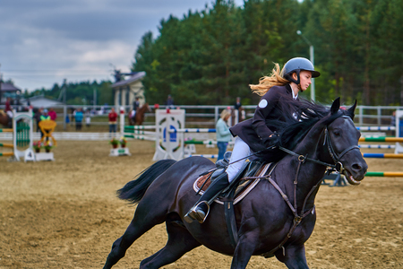 Young woman jockey in white black dress and black boots, takes part in equestrian competitions. Close-up. Stockfoto