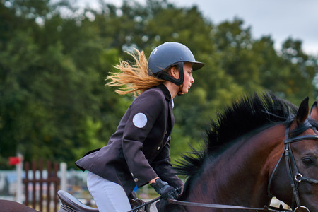 Young woman jockey in white black dress, takes part in equestrian competitions. Close-up. Stockfoto