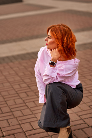 Portrait of a young beautiful woman with red hair. A cloudy day in the city. Фото со стока - 109161997