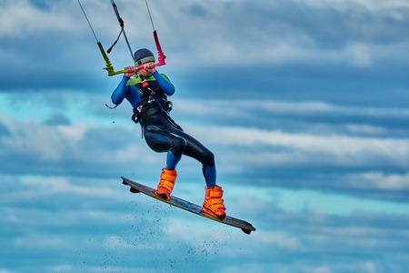 A male kiter jumps over a large lake. Close-up. Фото со стока - 109653027