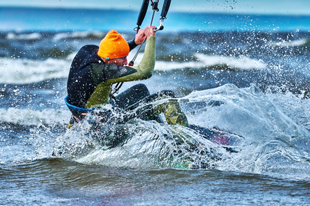 A male kiter slides on the surface of the water. Splashes of water fly apart. Close-up. Фото со стока