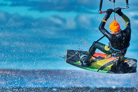 A male kiter jumps over a large lake. Close-up.